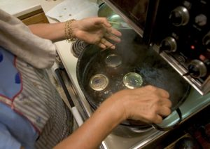 20050908CGB 6/X Mary Ann Brahler lowers a rack of jars, just filled with tomato sauce, into a pot of boiling water to get the lids to seal on with a vaccuum while canning the last of her tomatoes. 9/8/2005 CHRISTOPHER BARTH/FOR THE STAR-LEDGER